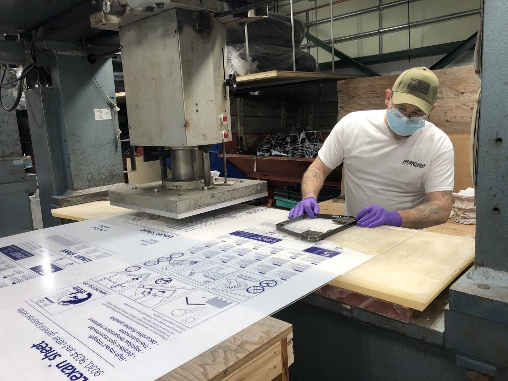 ProKnee employee with large Lexan Polycarbonate sheet for face shields