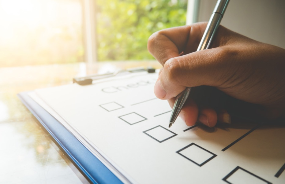 Stock photo of a hand with pen and paper checklist