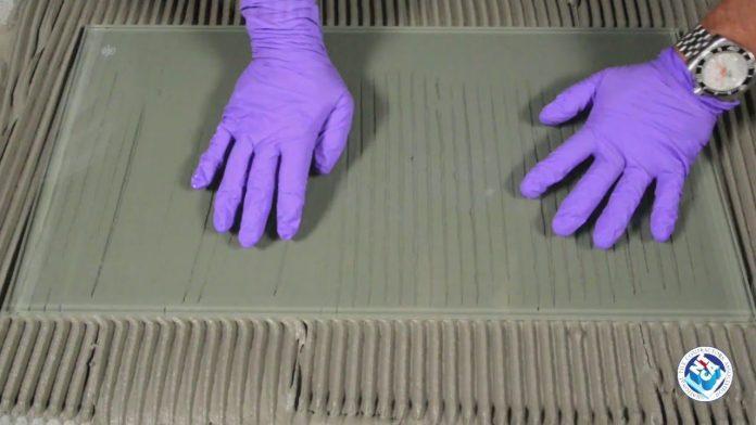 Gloved hands on glass over mortar